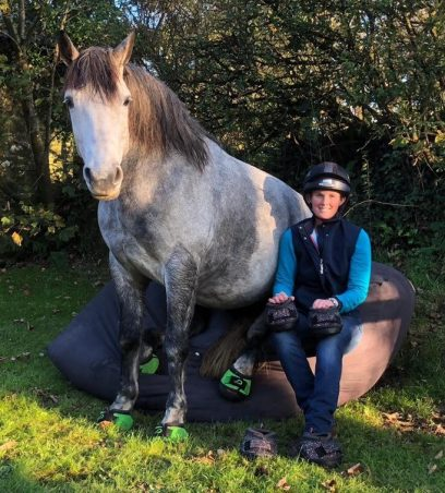 Emma Massingale and her horse sitting down in Cavallo Green Trek Horse Hoof Boots